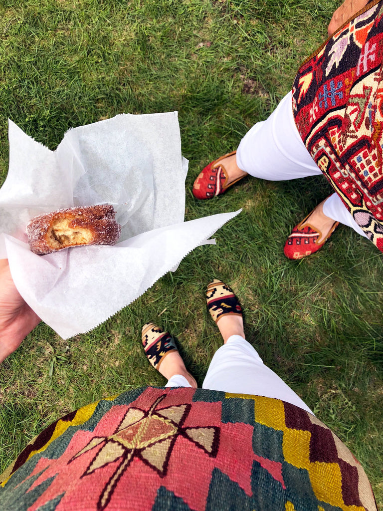 apple cider donut with team in kilim aprons and womens kilim slides and womens kilim loafers at brimfield antique market.