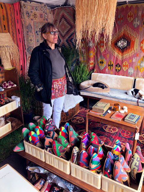 milicents mom preparing for customers surrounded by kilim carpets and standing next to displayed mens kilim loafers and womens kilim loafers.