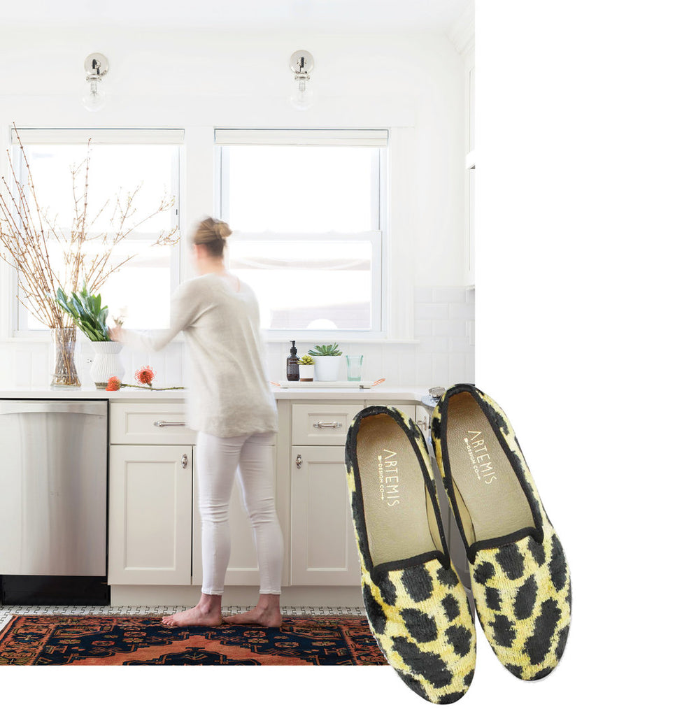 Sarah Scales in white kitchen on kilim carpet paired with leopard print McNeill velvet smoking shoes.