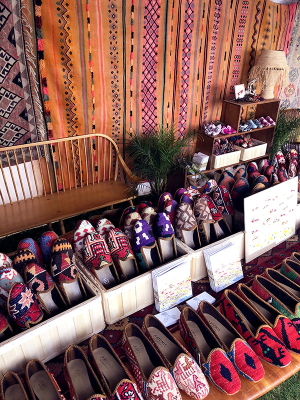 mens kilim loafers displayed with womens kilim loafers surrounded by kilim carpets.