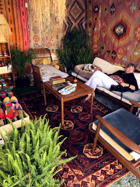 antique carpet books displayed next to silk loafers on table on kilim carpet surrounded by whicker furniture and kilim rugs.