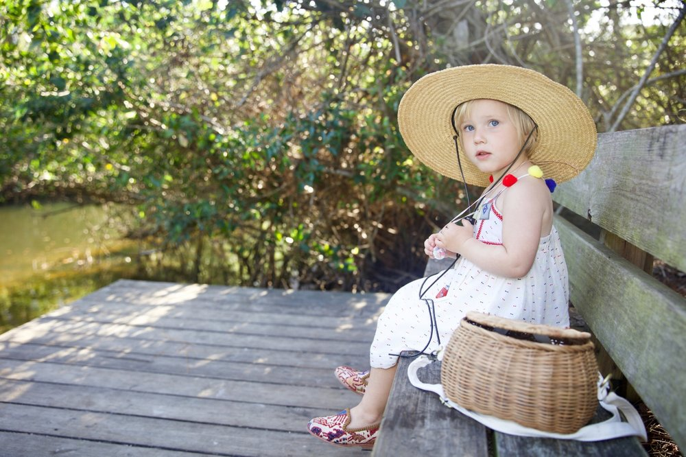 Madeline in colorful pom pom hat and in sumak kilim loafers, part of childrens shoes collection.