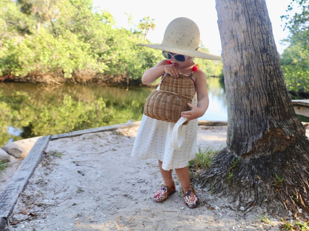 Madeline in colorful pom pom hat by lake and in sumak kilim loafers, part of childrens shoes collection.