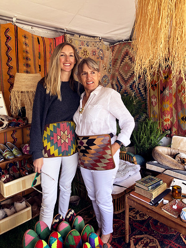 artemis team in kilim aprons and womens kilim loafers surrounded by kilim carpets and mens kilim loafers at brimfield antique market.