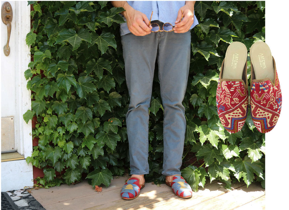 Model Lincoln in blue tones with mens kilim slippers in front of green plant.