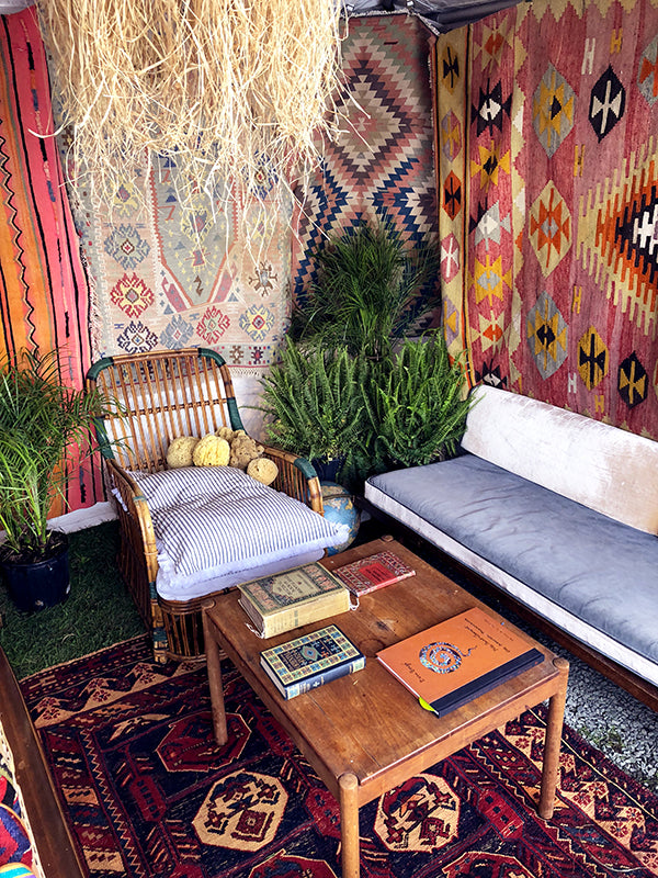 antique carpet books displayed on table on kilim carpet surrounded by whicker furniture and kilim rugs.