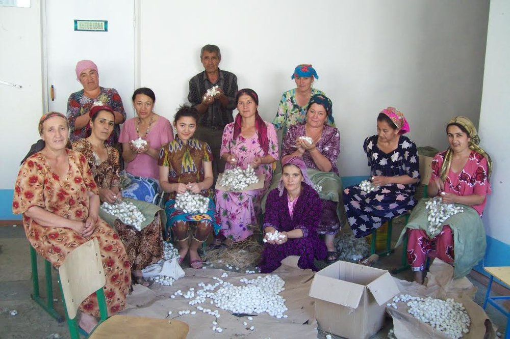 photograph of silk ikat weavers in uzbekistan in colorful dresses and headscarves.