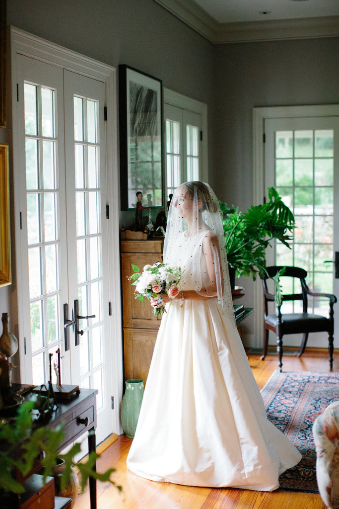 bride wearing her wedding dress and pearl velvet slippers looking out the window holding her bouquet.