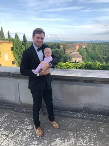 man-wearing-carpet-loafers-and-tux-holding-baby-italy