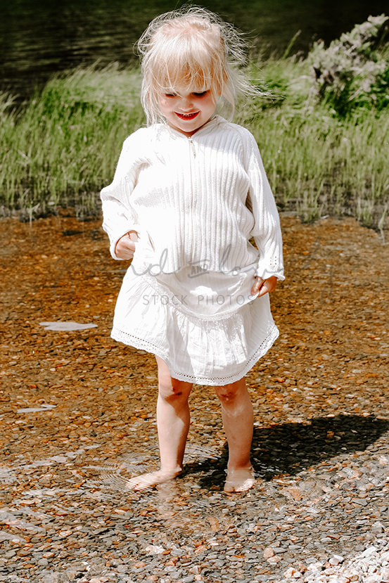 Styled Stock Photography | Blonde Child Paddling with skirt hitched | Lifestyle | Parenting - Grand & Lovely Stock styled photography desktops lifestyle screens desktops stationary