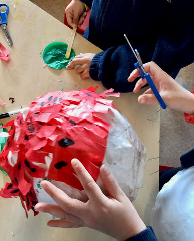 Kids decorating strawberry pinata box