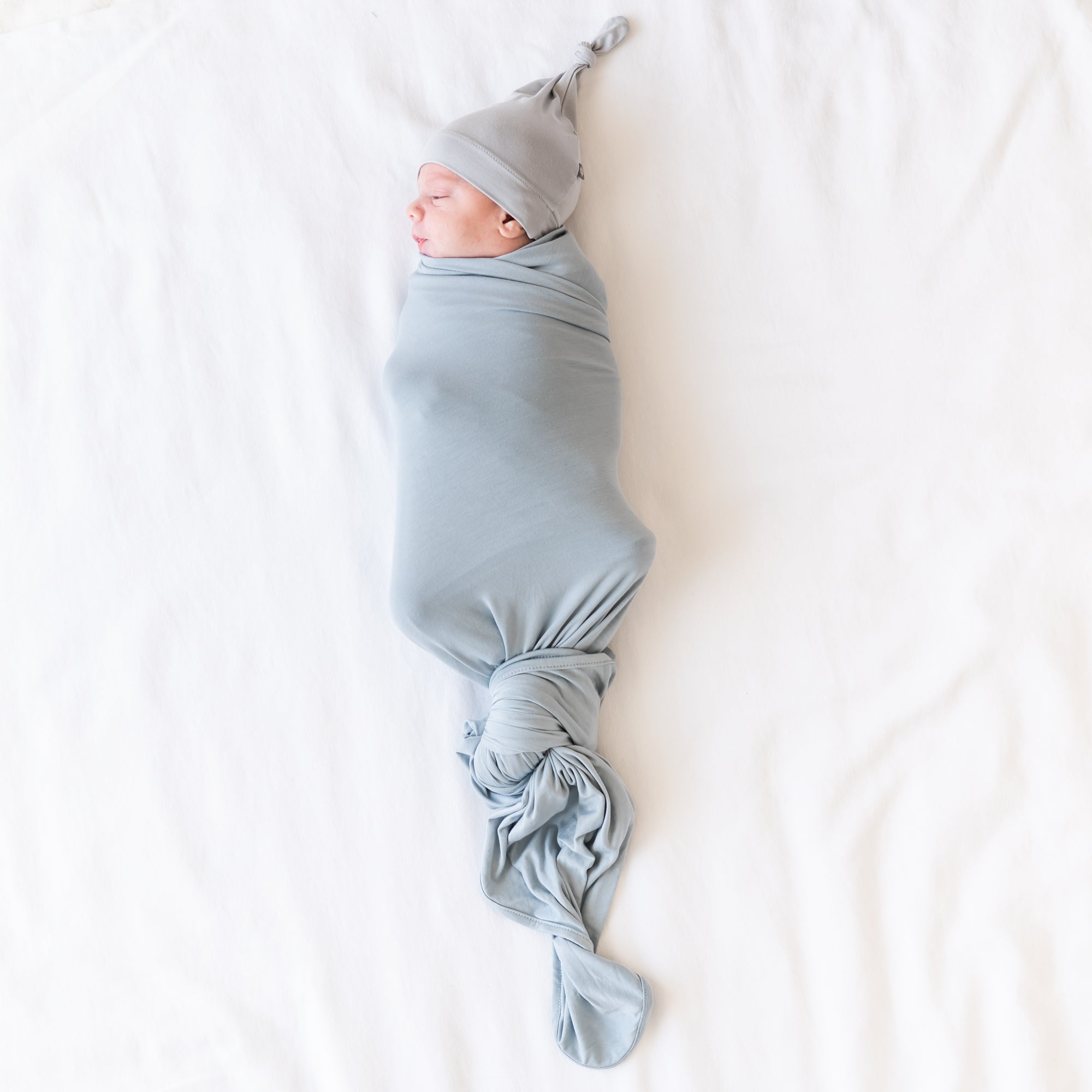 Baby being swaddled in blue grey swaddle and grey hat