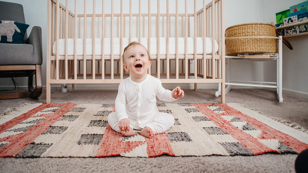 smiling baby sitting on floor in front of crib