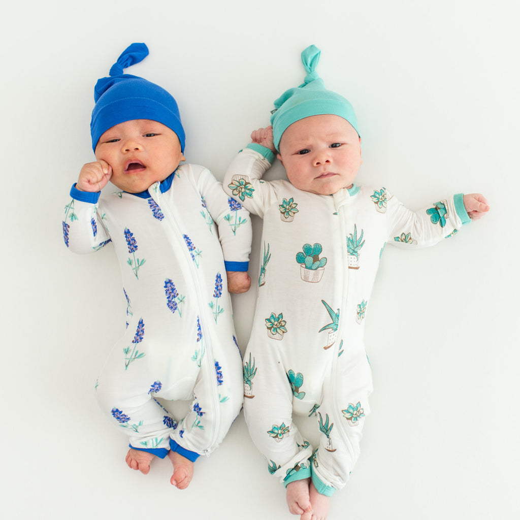 Asian and caucasian baby laying on back in bluebonnet print and succulent print pajamas