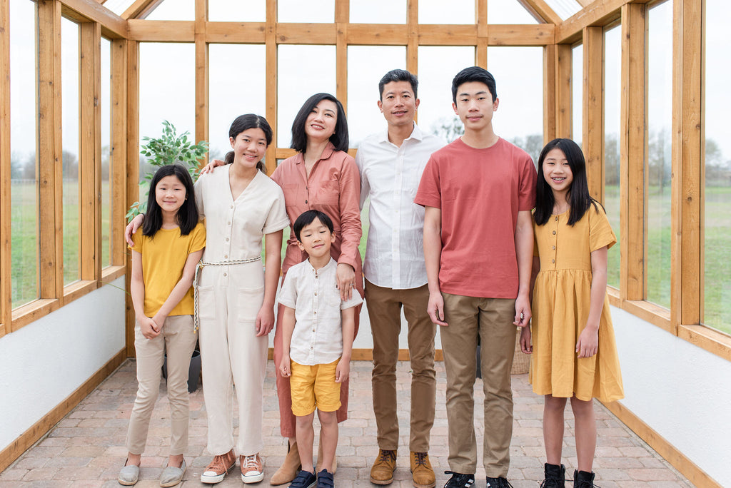 asian family of seven inside a greenhouse wearing matching outfits