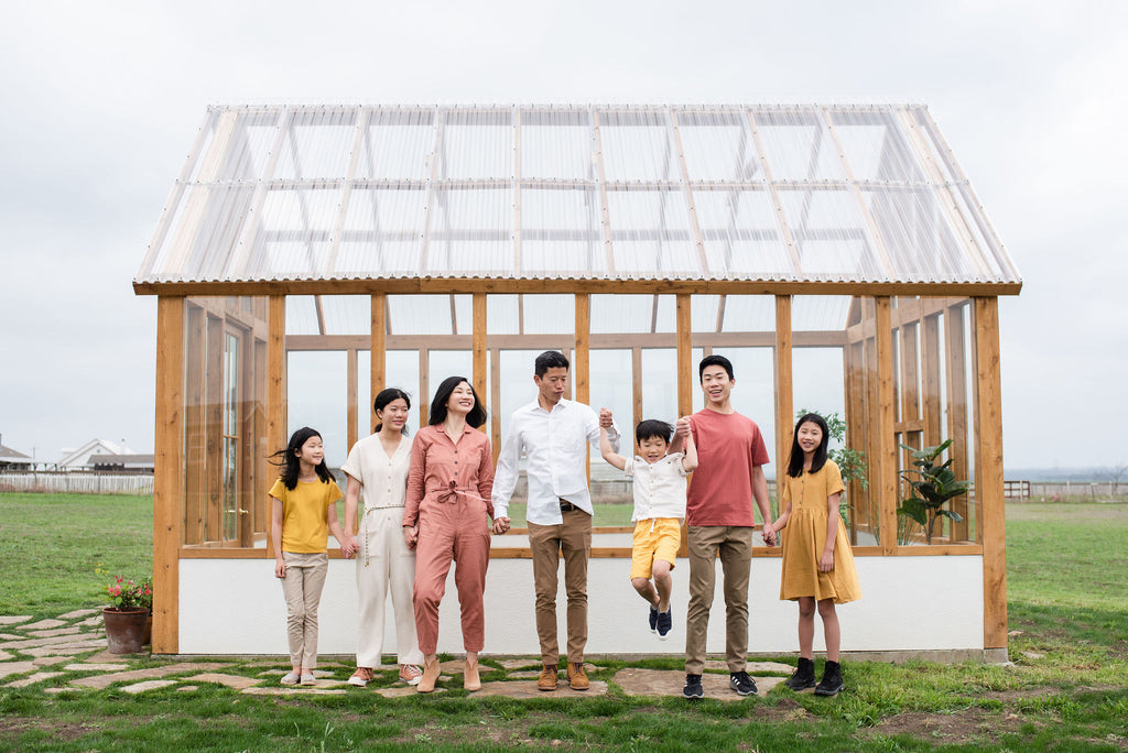 asian family of seven standing outside of a greenhouse holding hands