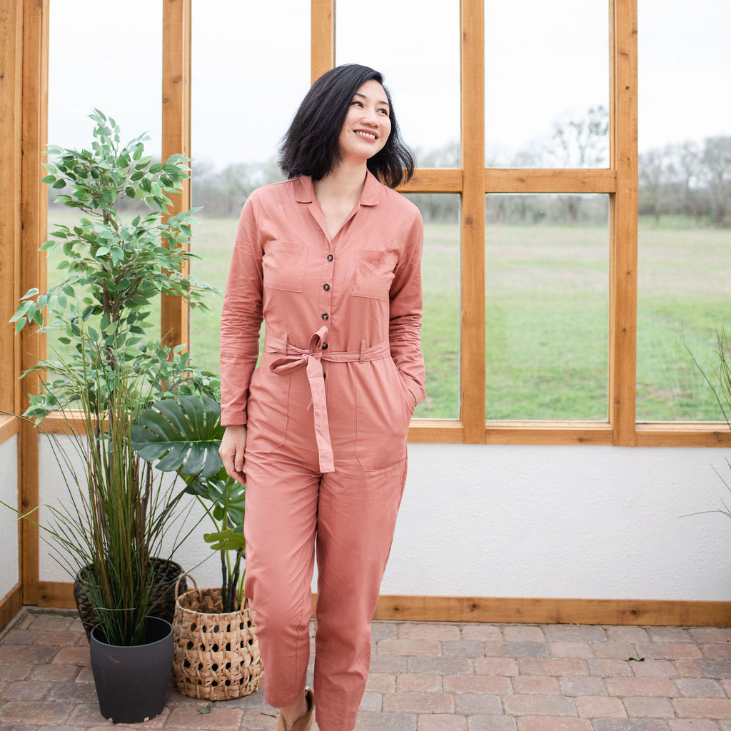 asian woman walking with one hand in pocket wearing pink inside a greenhouse