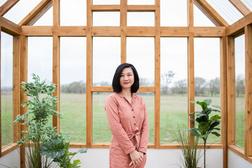 Asian woman standing in a greenhouse wearing a pink jumpsuit