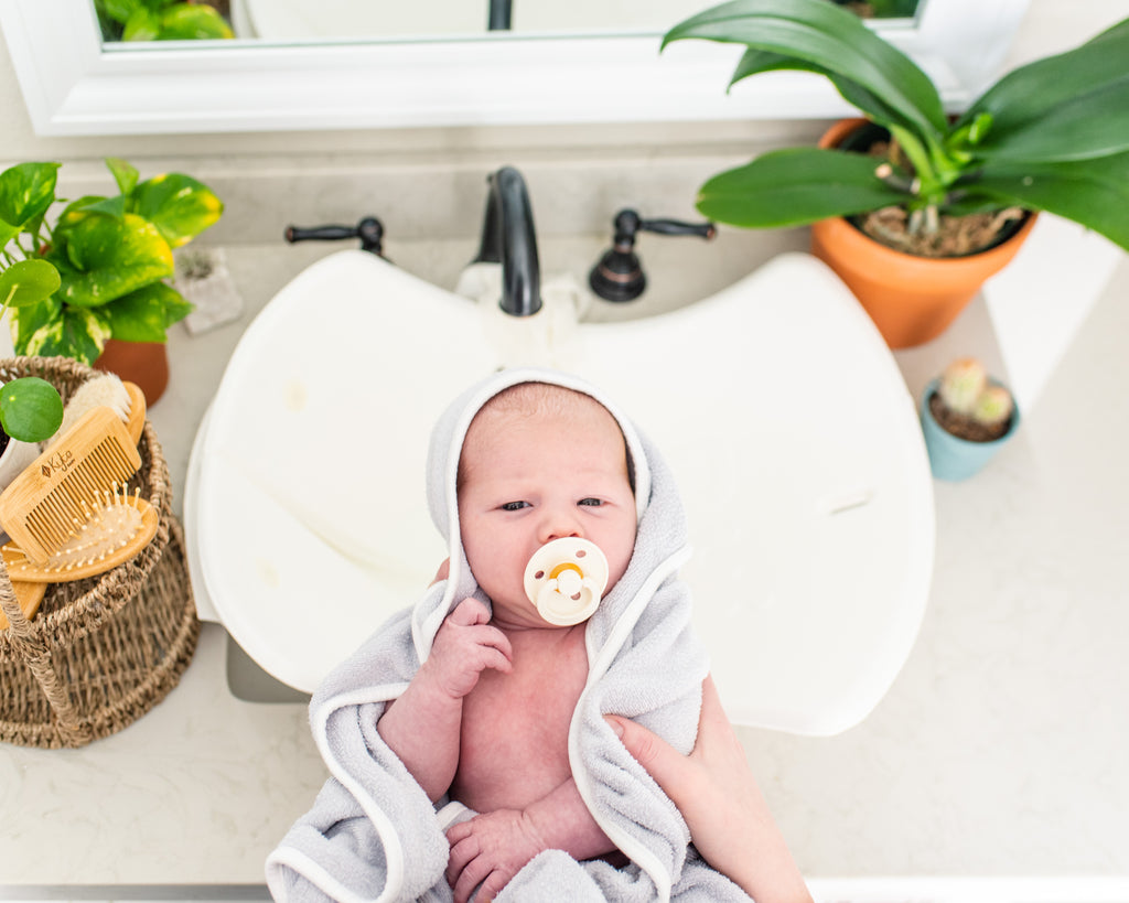 baby wrapped in towel with paci in mouth above bathroom sink