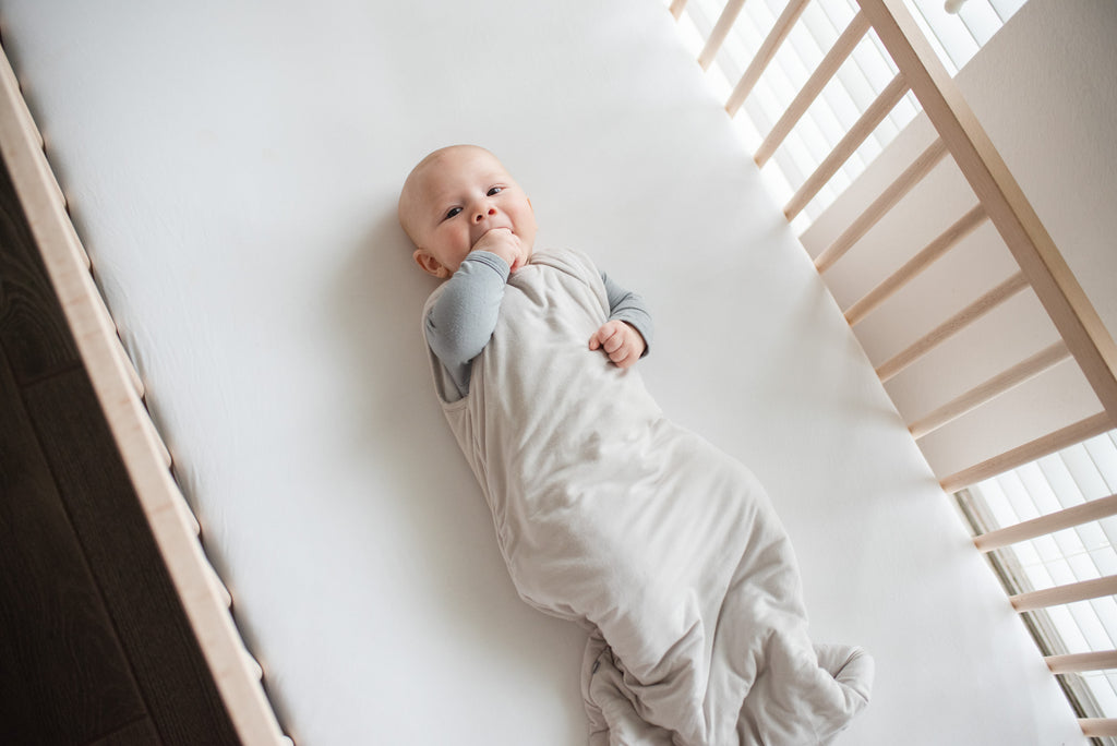 Baby laying in crib chewing fingers