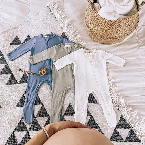 mom's hand on pregnant belly over kyte baby footies laid out on the bed