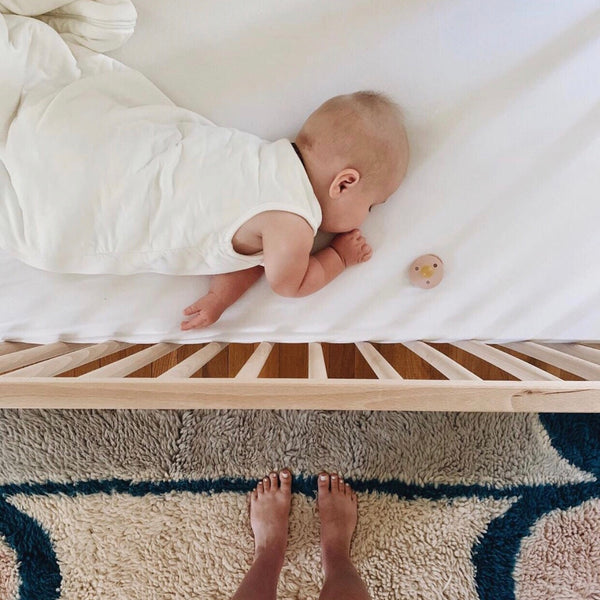baby sleeping in crib with mom standing in front