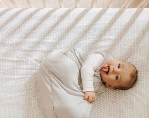 baby wearing kyte baby sleep bag and sticking out tongue in crib