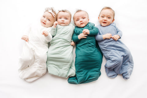four babies wearing sleep sacks and looking up at the camera