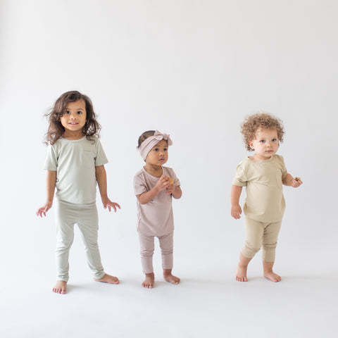 Three Children Modeling Unisex Tees and Leggings in Aloe, Sunset, and Wheat