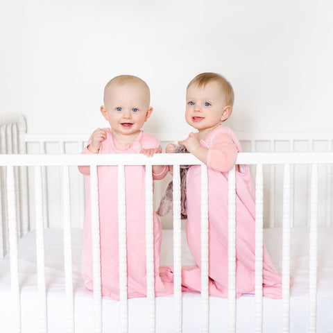 smiling twin babies standing up in crib