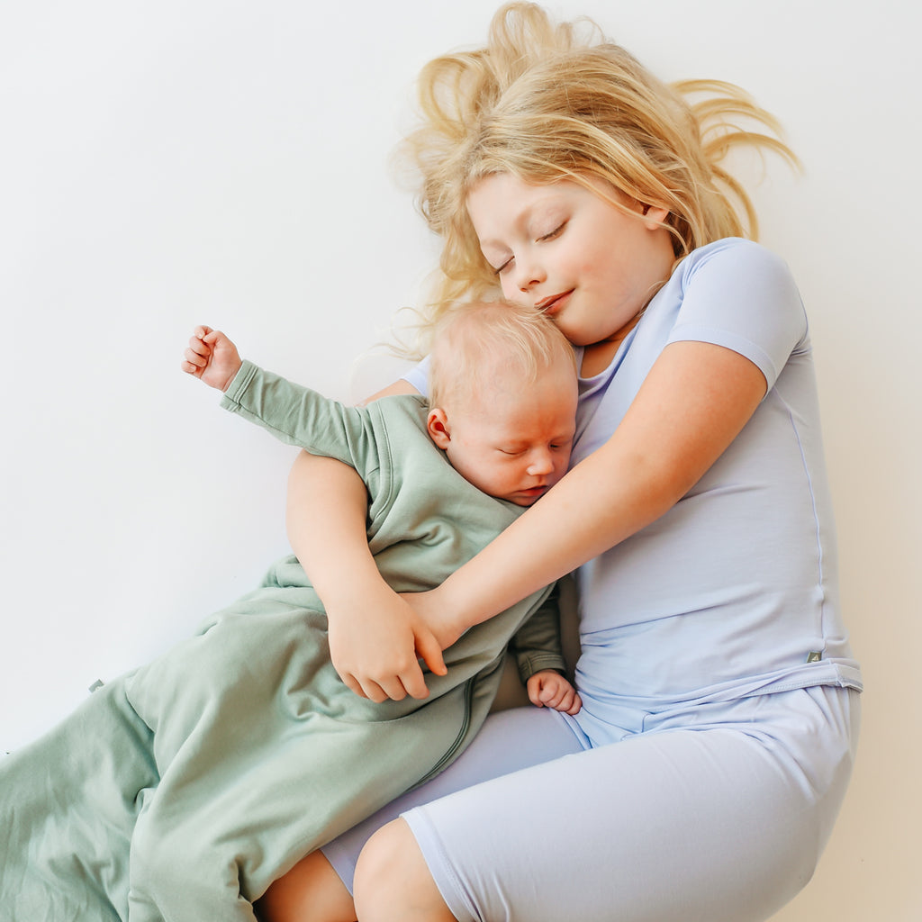 toddler and newborn sibling cuddling and sleeping in pajamas