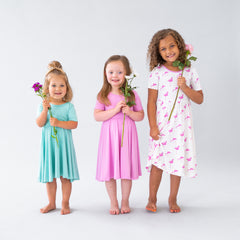 Three girls lined up holding flowers and wearing Kyte BABY Toddler Twirl Dress in Jade, Bubblegum and Flamingo