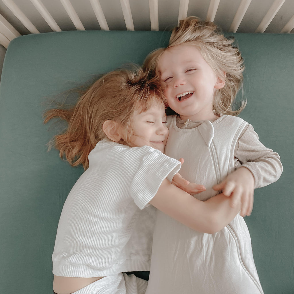 two toddlers laying in twin bed one is wearing a white shirt one is wearing a sleep bag