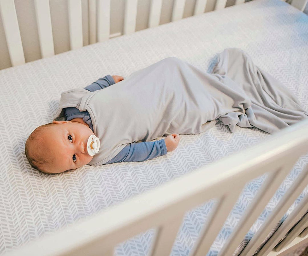 0.5 TOG Sleep Bag on Baby Laying in Crib and Staring off in Distance