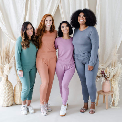 Four women modeling Women's Jogger Sets in Pine, Spice, Mulberry, and Charcoal