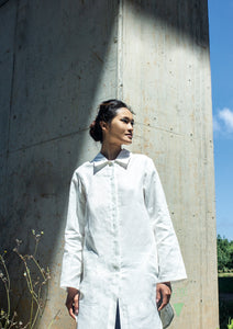 woman with white linen shirt which is also a dress.