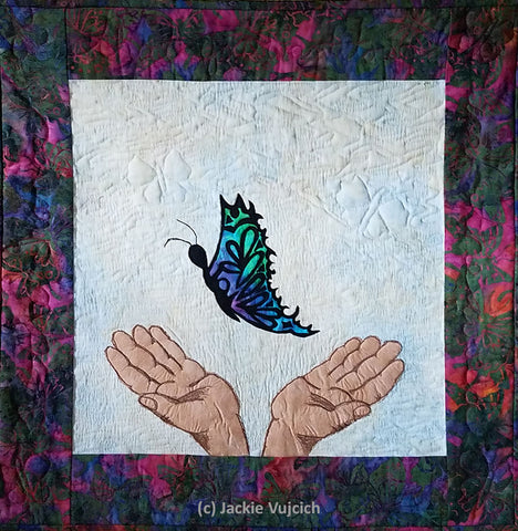 If you love them set them free pictorial art quilt  by Jackie Vujcich depicting to hands letting a butterfly fly free. Featured in a blog post by Jackie Vujcich of Colorado Creations Quilting
