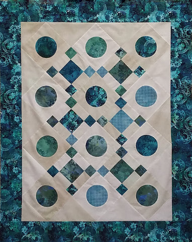 Teal-blue circles and squares are set on a cream background in this quilt by Jackie Vujcich of Colorado Creations Quilting.  Jackie teaches classes on making this technique simple