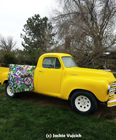 1950 yellow Ford truck with a quilt hung over the side.  Savvy Strips quilt pattern by Jackie Vujcich is available at Colorado Creations Quilting