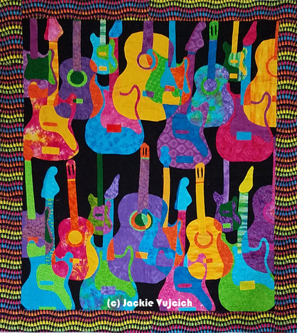 Guitars in many viabrant colors are depicted in this quilt made and  featured in a blog post by Jackie Vujcich of Colorado Creations Quilting