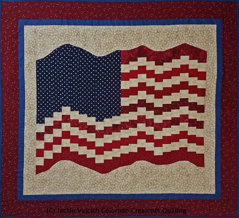 This quilt by Colorado Creations Quilting features a United States flag blowing in the breeze.