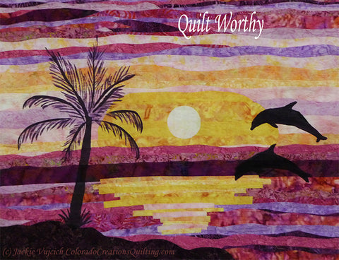 Dancing Dolphins quilt by Colorado Creations Quilting features dolphins jumping out of the water with a sunset in the background and a silhouette of a palm tree on shore.