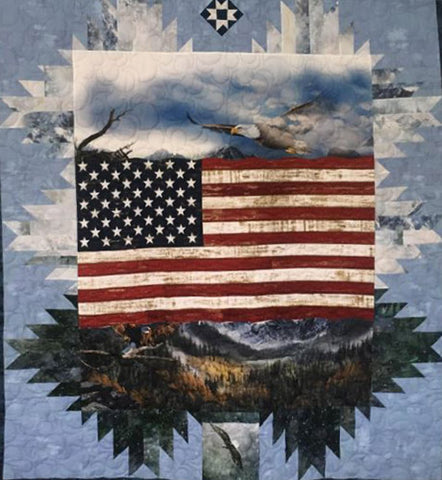 The quilt features the United States flag surrounded by bald eagles flying in a blue sky and green mountains below.