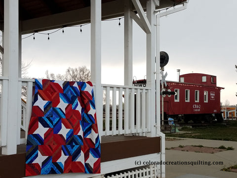 Red, white and blue quilt hangs over the railing of a white gazebo with a red caboose in the background.