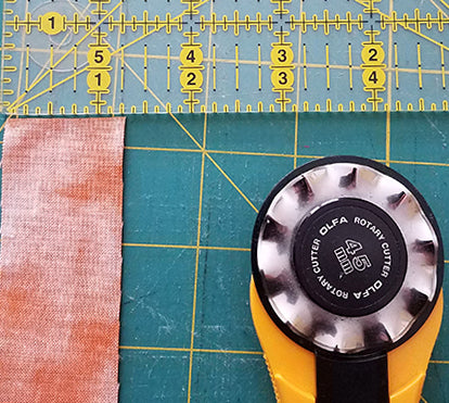half in strips and a rotary cutter with a scallop blade