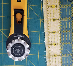 image shows the binding strip and a rotary cutter with a scallop edge