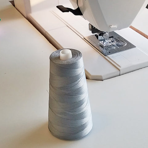 Large cone of gray thread new a sewing machine
