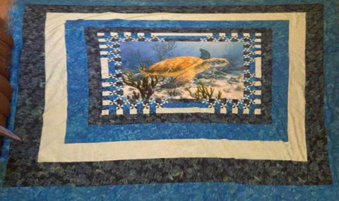Quilt featuring a sea turtle in the center.