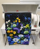 Image of fabric being loaded into a Mangle ironing machine by Colorado Creations Quilting