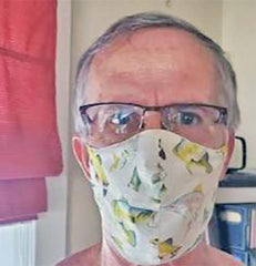 Marth G.'s husband wearing a face mask made of quilting cotton featuring fish that she got from Colorado Creations Quilting